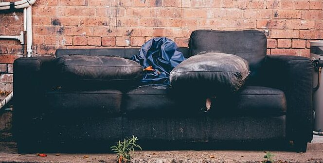 black-3-seat-sofa-beside-brick-wall-e1586791567806.jpg
